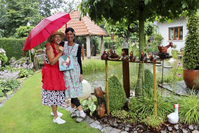 Auch das gehört zum Landleben: Ein kräftiger Guss von oben, der das Gießen überflüssig macht. Renate Wischinski (l) und Doris Angenendt (r) nehmen es mit Humor und freuen sich schon auf ihre Besucher am Ausstellungswochenende. NN-Foto: CDS