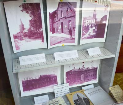 Der Schaukasten mit alten Fotos im Schaufenster der Bäckerei Dams auf der Dorfstraße, von dem sich die Männer vom Haus der Veener Geschichte weitere Erkenntnisse erhoffen.