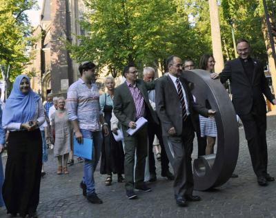 """Vertreter dreier Religionen rollten den """"Engel der Kulturen"""" gemeinsam über den Kapellenplatz.  Foto: Bischöfliche Pressestelle / Christian Breuer"""